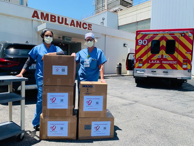 Hospital workers unloading a pallet of PPE equipment